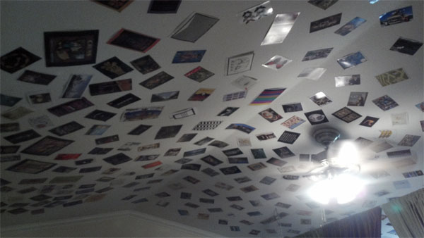 hundreds of postcards stapled to a vaulted ceiling